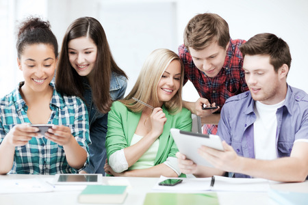 education, technology and internet - students looking at smartphones and tablet pc photo