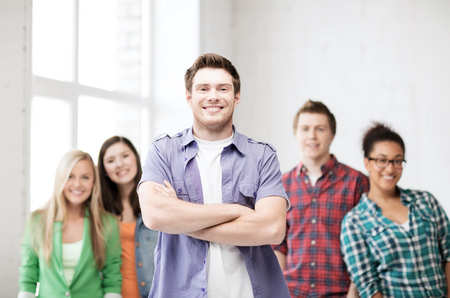 group leader: education concept - student boy with group of students at school
