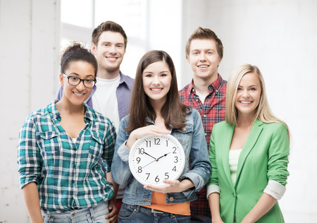 education and time concept - group of students at school with clock photo