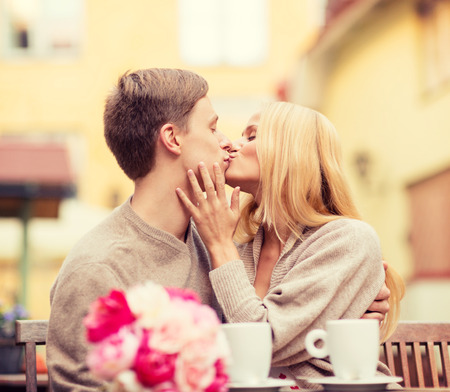 kissing couple: summer holidays, love, travel, tourism, relationship and dating concept - romantic happy couple kissing in the cafe