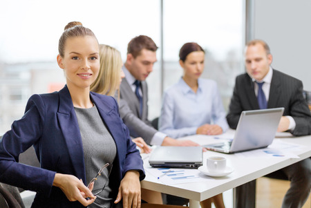 business, technology and office concept - smiling businesswoman with eyeglasses in office with team on the back photo