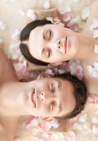 faces of couple in spa salon lying on the massage desks photo
