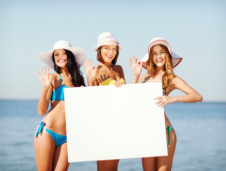 summer holidays and vacation - girls in bikinis holding blank white board on the beach photo