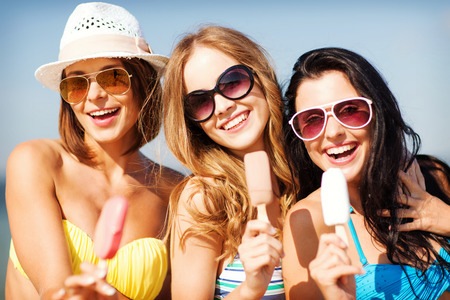 chilling out: summer holidays and vacation - girls in bikinis eating ice cream on the beach Stock Photo