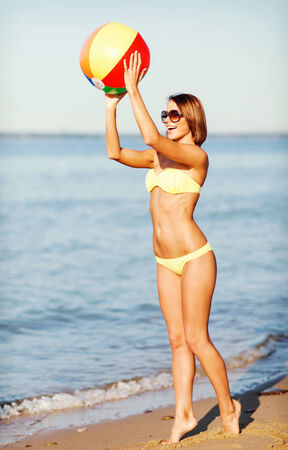 chilling out: summer holidays, vacation and beach activities concept - girl in bikini playing ball on the beach