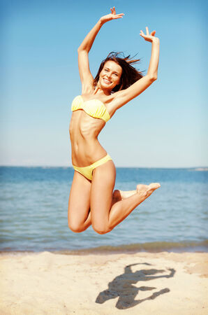summer holidays and vacation concept - beautiful woman in bikini jumping on the beach photo