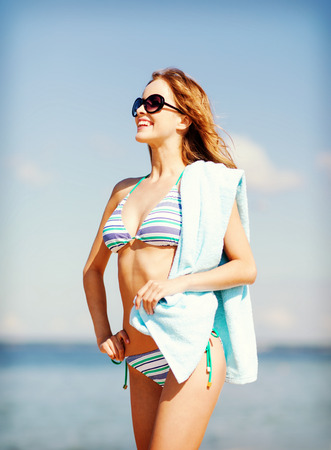 towel beach: summer holidays, vacation and beach concept - girl in bikini and shades on the beach
