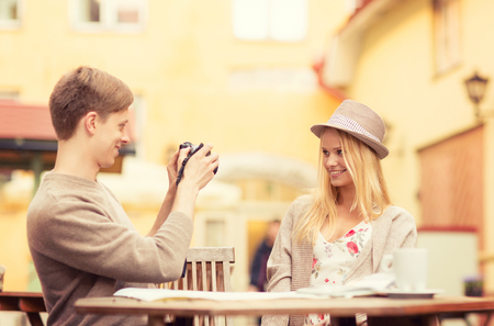summer holidays and dating concept - couple taking photo picture at cafe in the city photo
