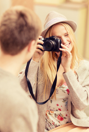 taking photograph: summer holidays and dating concept - couple taking photo picture at cafe in the city