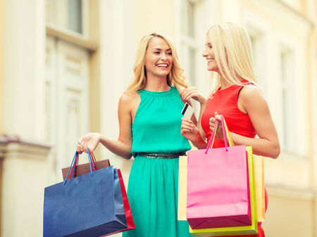 sale and tourism, happy people concept - beautiful women with shopping bags and credit card in the ctiy photo