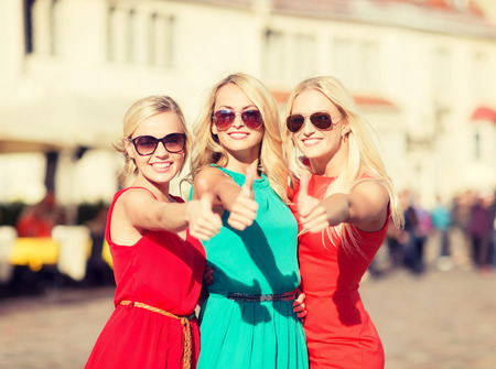 holidays and tourism, friends, hen party, blonde girls concept - three beautiful women in the city showing thumbs up photo