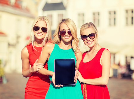 visitors: holidays and tourism concept - beautiful blonde girls toursits showing tablet pc with blank screen in the city Stock Photo