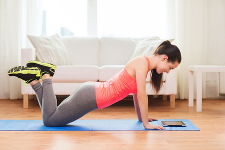 haciendo ejercicio: fitness, hogar, tecnolog�a y el concepto de dieta - adolescente sonriente haciendo flexiones y mirando a la tableta pc ordenador en casa