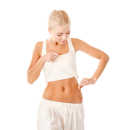 pinch: fitness and diet concept - beautiful sporty woman measuring fat level on her waist Stock Photo