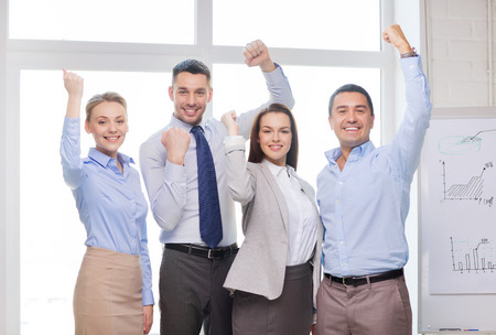 business, office, success and victory concept - happy business team celebrating victory in office photo