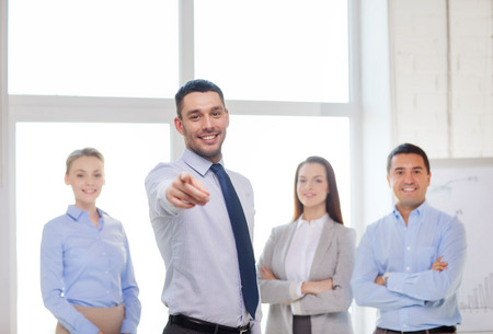 inviting: business and office concept - smiling handsome businessman with team in office pointing finger at you Stock Photo