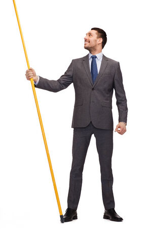flag pole: business and advertisement concept - smiling businessman holding flagpole with imaginary flag Stock Photo