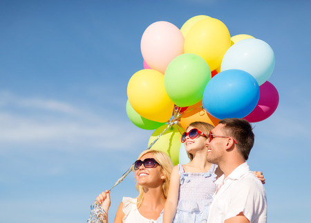 balloon love: summer holidays, celebration, children and people concept - happy family with colorful balloons outdoors