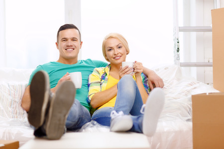 moving, home and couple concept - smiling couple relaxing on sofa with tea cups in new home photo