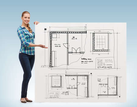 happiness, advertising and people concept - smiling young woman pointing hand board with blueprint photo