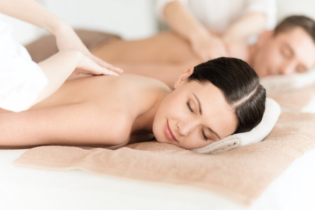 spa treatment: health and beauty, resort and relaxation concept - couple in spa salon getting massage Stock Photo