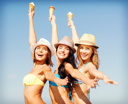 summer holidays and vacation - girls in bikinis eating ice cream on the beach photo
