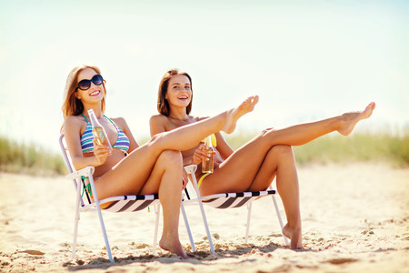 beach chairs: summer holidays and vacation - girls in bikinis with drinks on the beach chairs