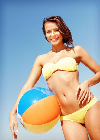 beach ball girl: summer holidays, vacation and beach activities concept - girl in bikini with ball on the beach