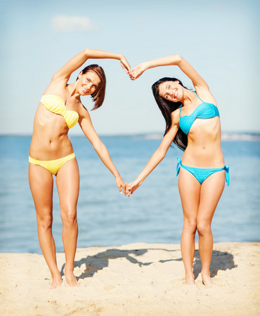 summer holidays and vacation - girls in bikinis making heart shape with hands on the beach photo