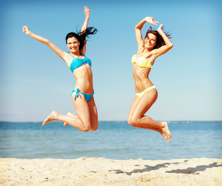 long legs: summer holidays and vacation concept - beautiful girls in bikini jumping on the beach