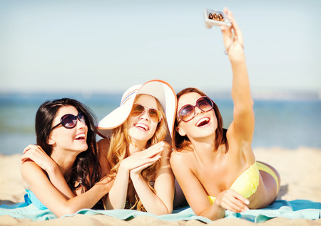 digi: summer holidays, vacation and beach concept - girls in bikinis taking self photo on the beach