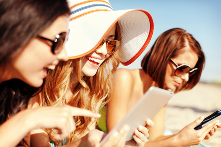 lifestyle: summer holidays, technology and internet concept - girls in bikinis with tablet pc sunbathing on the beach