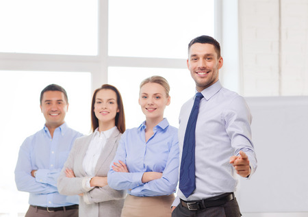business and office concept - smiling handsome businessman with team in office pointing finger at you Stock Photo