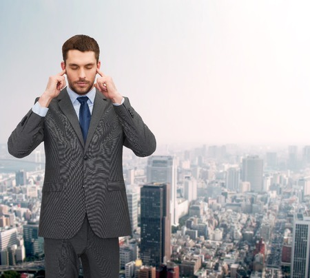 businss, office and education concept - annoyed businessman covering his ears with his hands photo