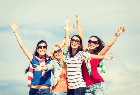 teenagers laughing: summer, holidays, vacation, happy people concept - beautiful teenage girls or young women having fun on the beach Stock Photo
