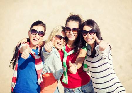 summer, holidays, vacation, happy people concept - beautiful teenage girls or young women showing thumbs up photo