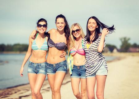 niñas en bikini: verano, vacaciones, vacaciones, feliz a la gente concepto - grupo de chicas en bikini caminando por la playa Foto de archivo
