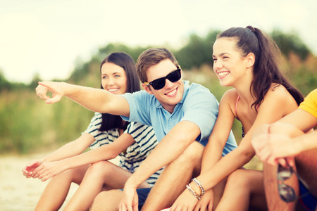 somewhere: summer, holidays, vacation, happy people concept - group of friends pointing somewhere on the beach
