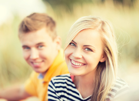 happy young people: summer, holidays, vacation, happy people and dating concept - couple or friends sitting at the sea side