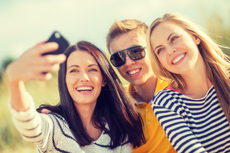 summer, holidays, vacation, happy people concept - group of friends taking photo picture with smartphone photo