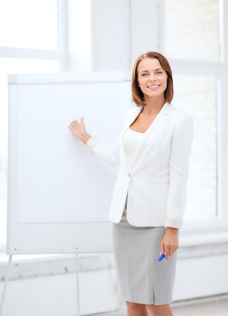 business and education concept - smiling businesswoman showing flipchart photo