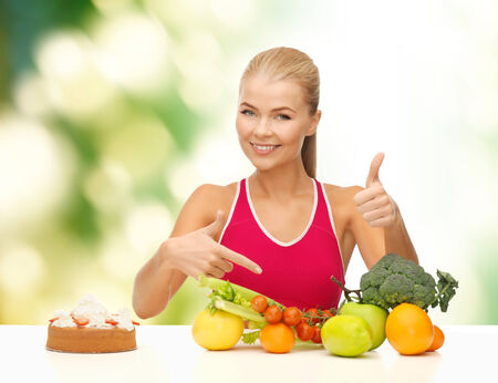 bad diet: fitness, healthcare and diet concept - smiling woman with fruits and cake pointing at healthy food
