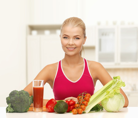 remise en forme, l'alimentation et le concept de soins de santé - jeune femme souriante avec des aliments biologiques sur la table