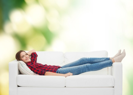 home, leisure and happiness concept - smiling teenage girl lying on sofa