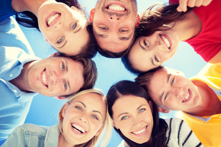people celebrating: summer, holidays, vacation, happy people concept - group of teenagers looking down