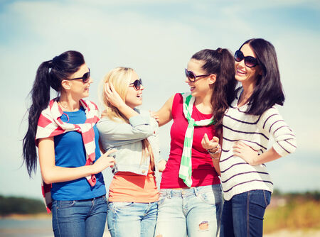 summer, holidays, vacation, happy people concept - beautiful teenage girls or young women having fun on the beach photo