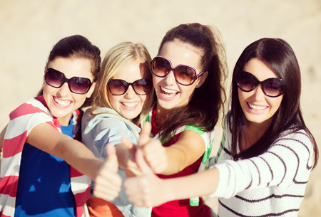hang up: summer, holidays, vacation, happy people concept - beautiful teenage girls or young women showing thumbs up