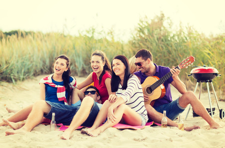 group of teenagers: summer, holidays, vacation, music, happy people concept - group of friends with guitar having fun on the beach