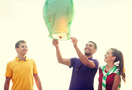 summer, holidays, vacation, happy people concept - group of friends with chinese sky lanterns on the beach photo