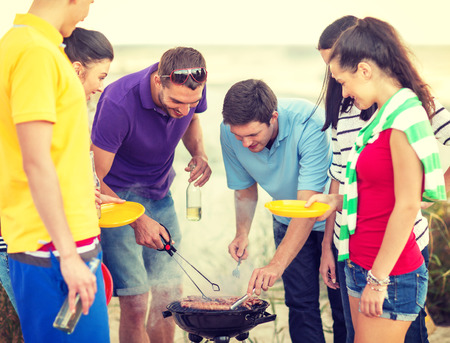 barbeque: summer, holidays, vacation, happy people concept - group of friends having picnic and making barbecue on the beach